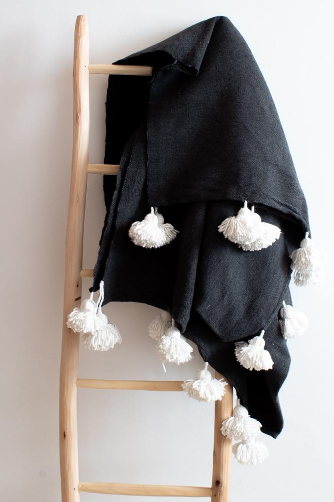 Graue Tagesdecke mit Pompoms
