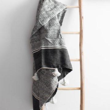 Gemusterte Pompom Decke in schwarz-weiß
